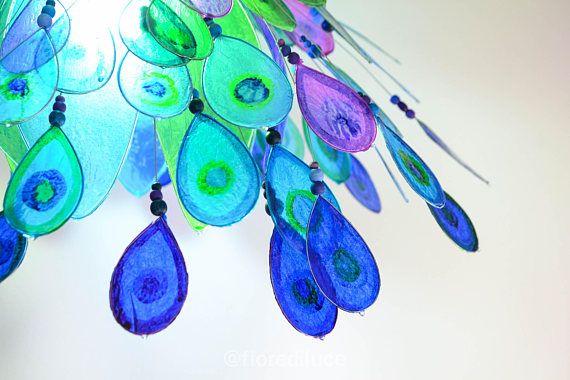 Ispirato al bellissimo ed elegantissimo pavone, prende spunto dai suoi colori e dalle sue piume.  Il lampadario è interamente creato a mano utilizzando carta trattata con resina, che dona laspetto vetrificato rendendo la carta resistente ed infrangibile. Su una struttura sottostante di petali colorati di blu, azzurro, verde e giallo prendono vita numerose piume colorate a mano con colori speciali per vetro, montate su bastoncini di filo di ferro e decorati con perle di legno e pietre color…