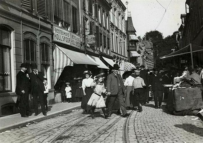 1905. Drukke Lange Jansstraat met kramen. Links naast Hollands Spoor, glazenwasser Proper (bestaat nog altijd)