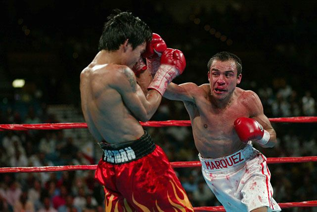 Photo: HBO Fight: Juan Manuel Marquez (White Shorts) Vs. Manny Pacquiao (Red Shorts), WBA  super featherweight title & IBF featherweight title. Date: May 5th, 2004. Place: MGM Grand, Las Vegas, Nevada, United States. A controvercial draw, in which the only thing that determined this, was that on the first round, Manny knocked down Juan Manuel three times. Pacquiao got rocked the entire fight after the first round.