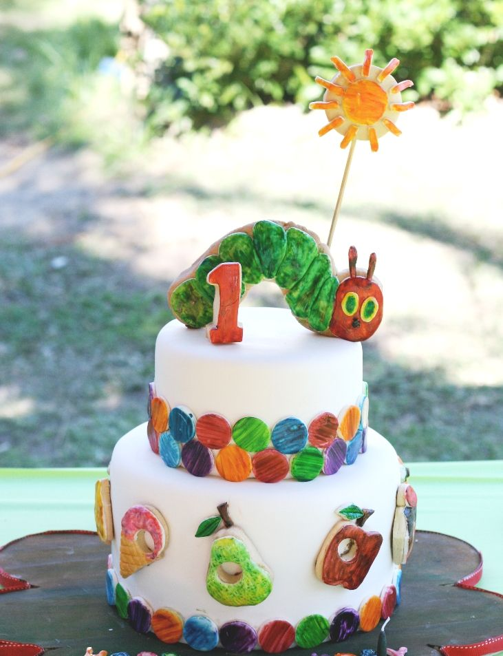 Sam's Hungry Hungry Caterpillar 1st Birthday Cake - By Nat and Jess . The food on the first tier, the caterpillar and the sun are butter cookies hand cut, covered wt fondant and hand painted.