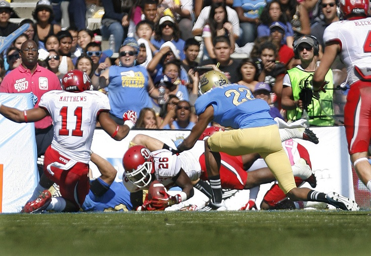 UCLA RB Steven Manfro (33) fumbles a punt into the end zone where Utah Utes defensive back Ryan Lacy (26) recovered for the Utes first TD, tying the score at 7-7.