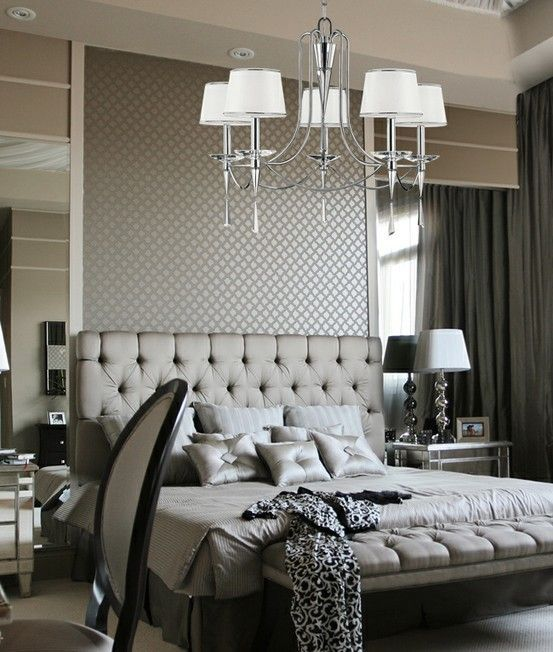 Glamorous gray bedroom with tufted headboard and mirrored accents.