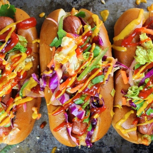 Korean Slaw Dogs: all-beef hot dogs loaded with Korean BBQ sauces, spicy kimchi, & sweet/tangy slaw, topped w/kickin' ketchup & mustard.