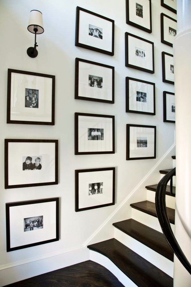 Display of black and white photos going up a staircase.
