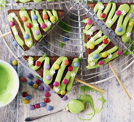 Christmas tree pops. Decorate wedges of chocolate sponge with green icing and Smarties to make festive cake pops on sticks - perfect for baking with kids