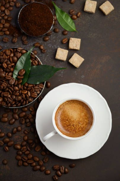 cup of fresh coffee with coffee beans on dark background