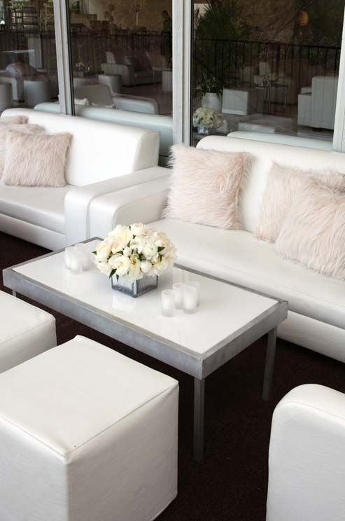 A sleek lounge area awaits guests, complete with candles, white leather furniture and fur throw pillows.