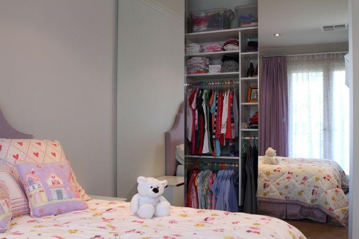 Custom designed wardrobes behind mirrored doors.