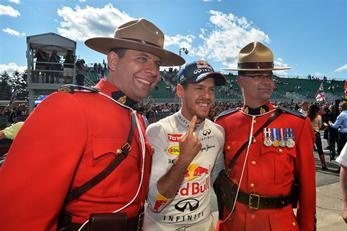 Race winner Sebastian Vettel (GER) Red Bull Racing flanked by two Canadian Mounties. Formula One World Championship, Rd7, Canadian Grand Prix, Race Day, Montreal, Canada, Sunday, 9 June 2013