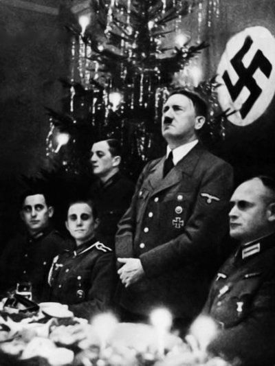 An extremely rare photograph, not even available on Google Images, of Adolf Hitler participating in Christmas celebrations alongside military personnel.