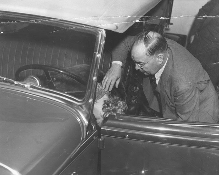 Captain Bert Wallis of the police homicide squad makes a check of the position of Thelma Todd's body where it was found in her car.