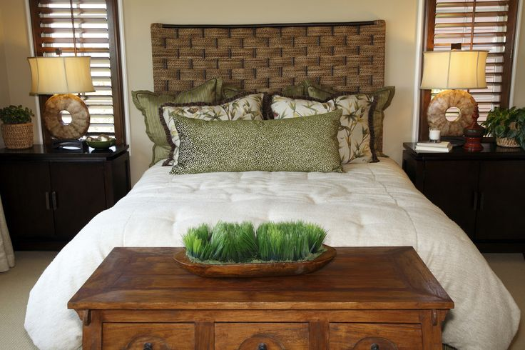Bedroom decked out in natural tones, with wood chest, white bedding, and dark wood bedside tables.
