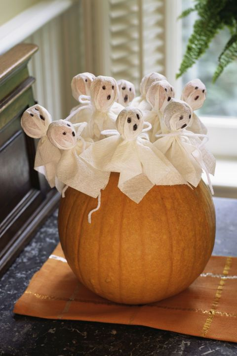 Halloween decor ideas: Cover lollipops with tissue paper for a ghost bouquet. And use a fresh pumpkin as the vase.