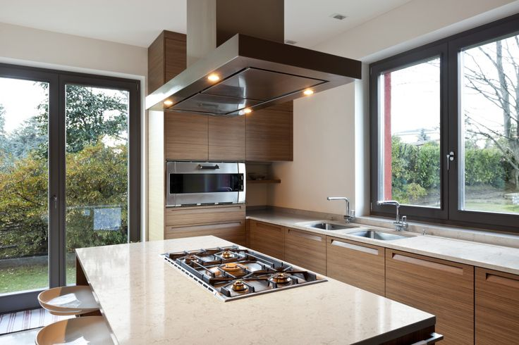 Modern Home Kitchen With Brown Cabinets, Cream Counter Tops, And Stove In  Island.