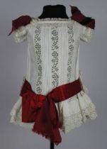 1880-1890. Kinderjurk van wit katoen, achter gerend, voorpand in prinsessenlijn, met broderie anglaise en kant, drie donkerrode satijnen strikken en één band met strik op de heup