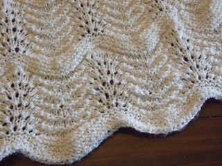 This is my variation on a common pattern… adding a border, plus bands of garter stitch to break up the field of feather and fan.
