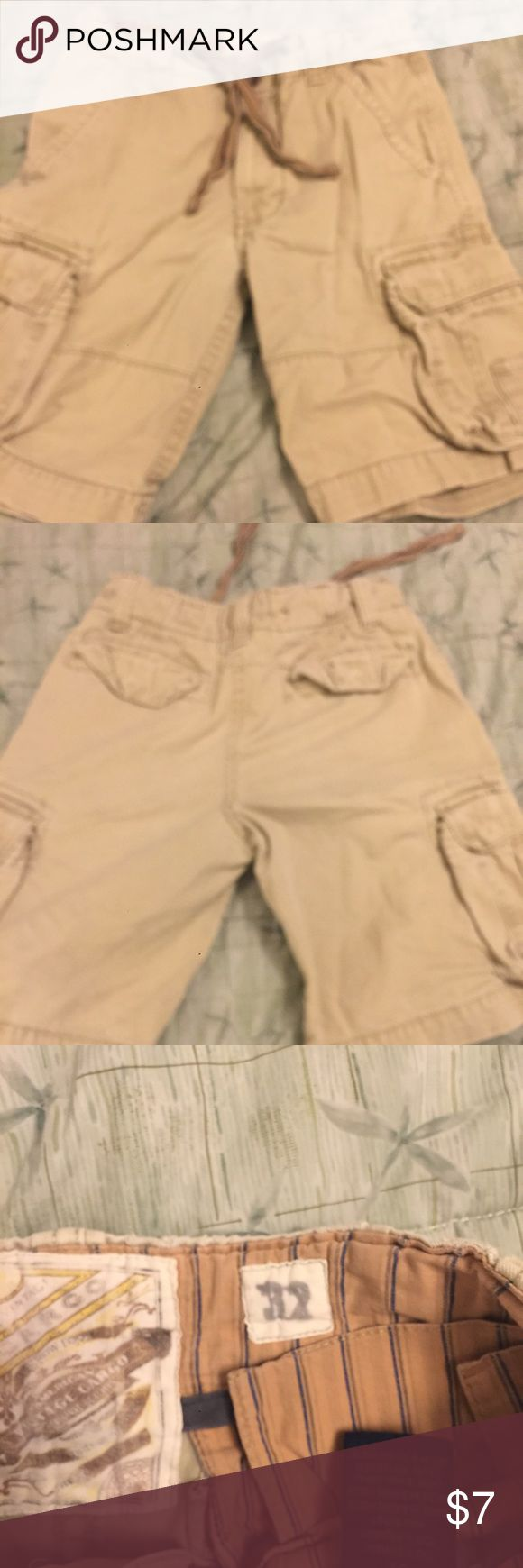 Tan Mens cargo shorts Size 32 Mens tan cargo shorts. Has drawstring and button closure. Has small spot that's only visible in the light by the front pocket. Priced to sell. Shorts Cargo