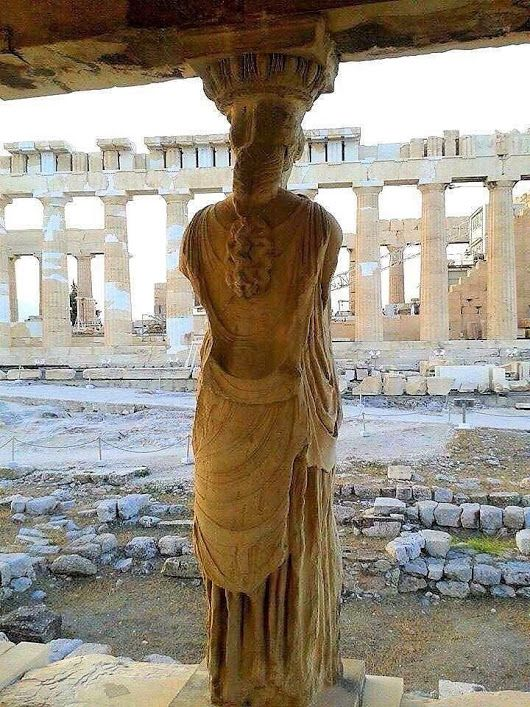 A rare vantage point from inside of the Erechtheum, behind one of the Caryatids on the 'Porch of  Maidens', which provides us with a glimpse of the iconic Parthenon.