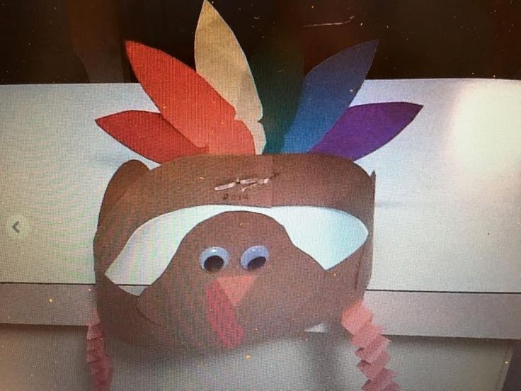 Adjustable turkey hat. Sketch a pear shaped head. Trace the child's hand for tail feathers or use a feather template. Trace a small cup or bowl, cut circle in half then scallop the edges of the straight edge for wings. Paper eyes may be used to prevent a choking hazard. Sketch & cut the red wattle. Cut two 9 inch strips orange strips for the legs then fold back and forth about 1/4 inch. Fringe ends of strips for feet. Use hole puncher & brass fasteners for an adjustable hat.