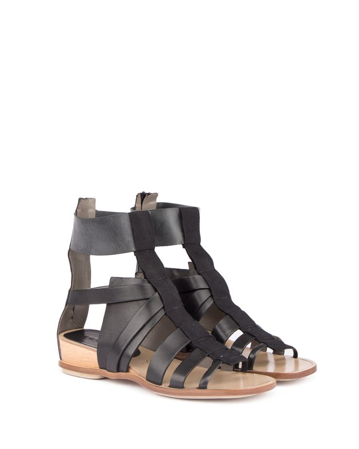 Flat sandal with leather bands, ankle height with zip opening on the heel. Small wood platform and leather sole