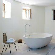 La salle de bains d\'amis avec une baignoire à débordement en pierre signée Boffi.