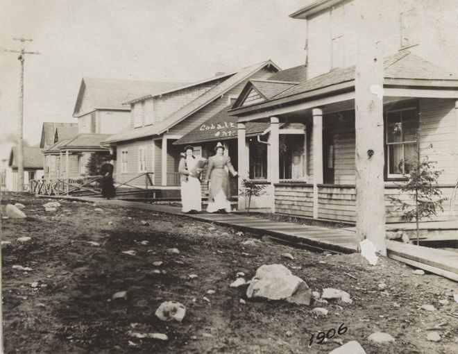 A photograph of Nurse Annie Saunders and another woman walking down a wooden sidewalk on Argentite street in Cobalt.