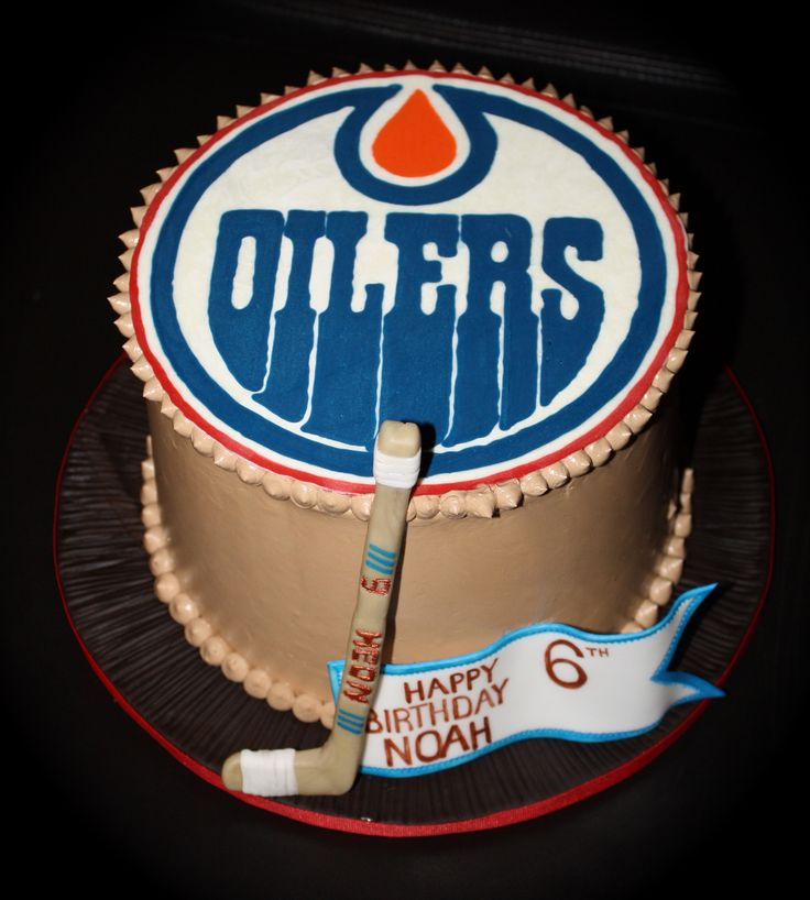 Noah's Edmonton Oilers Cake! - This cake is vanilla with cookies and cream filling and the outside is chocolate SMBC. The logo on top is a candy melt transfer (I was VERY pleased with it!!). The hockey stick is modeling chocolate with gumpaste tape and the banner is gumpaste. Thanks for looking!