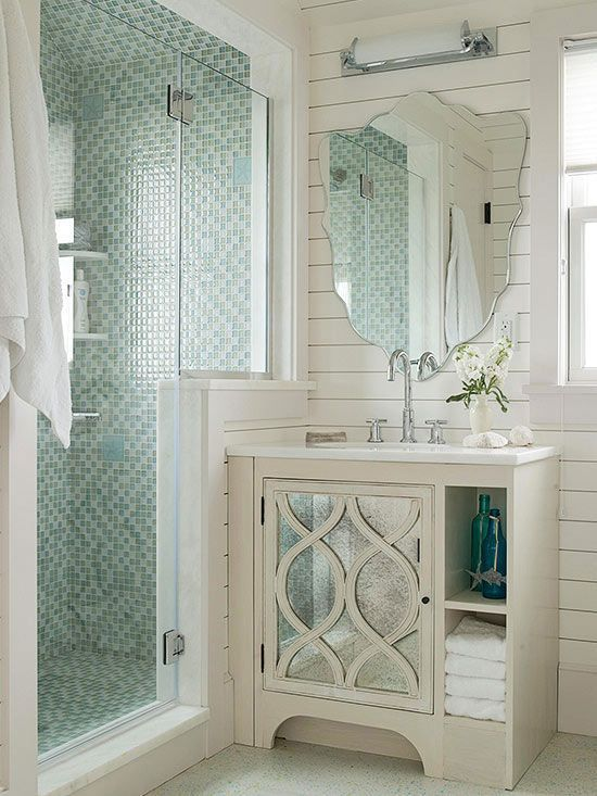 Expand a small bathroom's utility by designing a walk-in shower that provides a solid wall or walls for placing vanities or tubs. Seemingly an extension of the bathroom's board-clad walls, this knee wall accommodates a shallow vanity with a mirrored door. White painted walls, the shower's glass enclosure and tiled walls, and reflective surfaces encourage light to move around the space, causing the small bathroom to appear roomier.