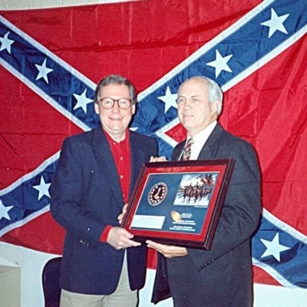 This man on the left, before the flag of a white supremacist enemy of the US, is the Republican leader in the US Senate.