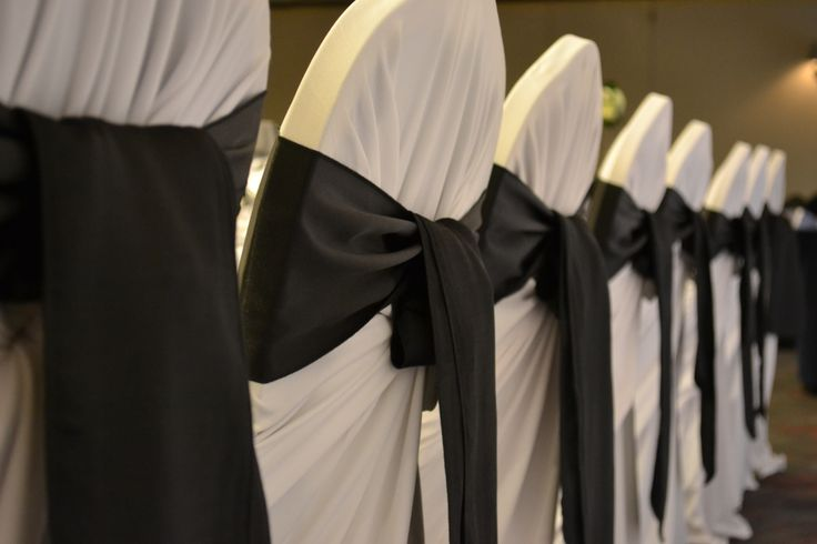 White tieback chair covers with black satin sashes. Styled by Greenstone Events.