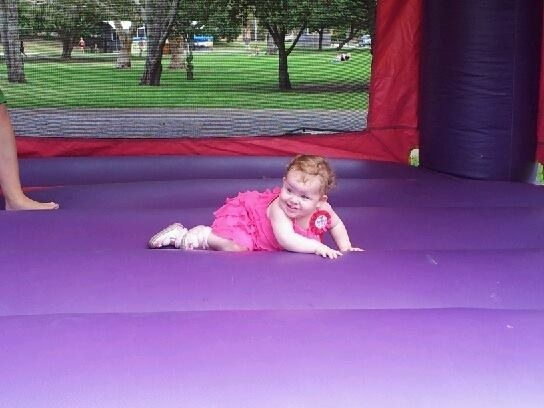 Lyla on her pink and purple jumping castle