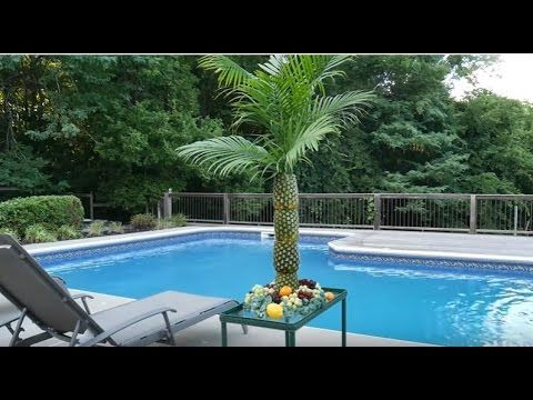 Perfect for tropical-themed parties, this palm tree serving tray and centerpiece is made of pineapples stacked on top of each other.
