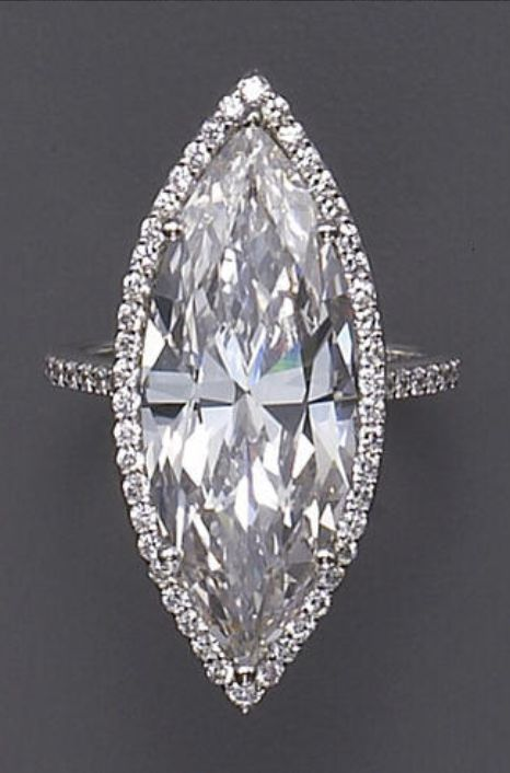 A diamond and platinum solitaire ring  centering a marquise-cut diamond weighing 10.27 carats within a frame of round brilliant-cut diamonds, completed by diamond shoulders and a plain hoop.