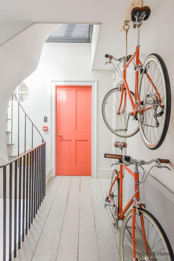 Huis inrichten Hal met witte vloer fietsen ophangen en kleurrijke deur…