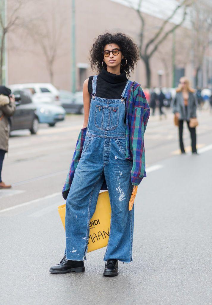 Photo by Christian Vierig/Getty Images      Imaan Hammam  デニムのサロペットパンツを履いた、人気モデルのイマン。トムボーイなサロペットパンツとチェック柄シャツの組み合わせに、ハイネックのノースリーブトップスとフープピアスが、大人のフェミニニティを加えている。彼女のトレードマークでもあるカーリーヘアや、オレンジ色のサング...