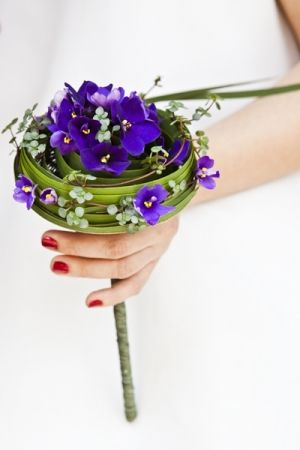 Weaving together metal wires in an umbrella shape with a small plate on the top, this structure was wrapped in paper thread before violets, Pilea, and Typha leaves were glued to the form to create this concentric bouquet. Floral Design: Sergey Malyuchenko, Photography: Katya Yeliseyeva