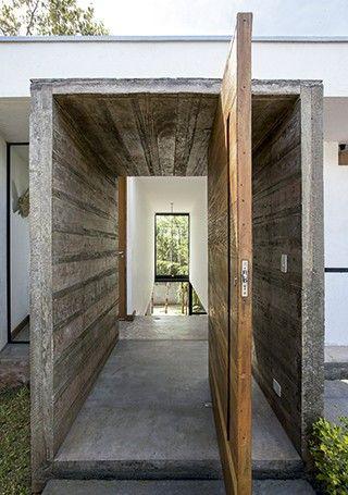 Da porta pivotante, de 1,40 m de largura, pode-se ver por meio de uma abertura as árvores do quintal, nativas do terreno (Foto: Marco Antonio/ Editora Globo)