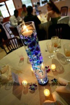 Blue orchids in tall vase with floating candle. Beautiful!