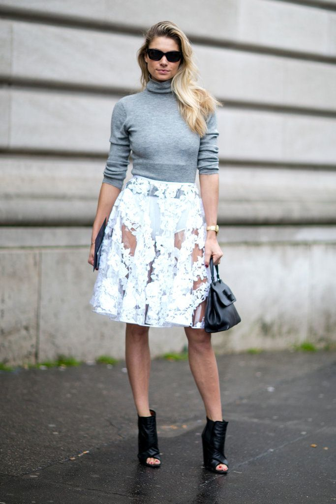A printed skirt paired with a turtleneck sweater and ankle boots.