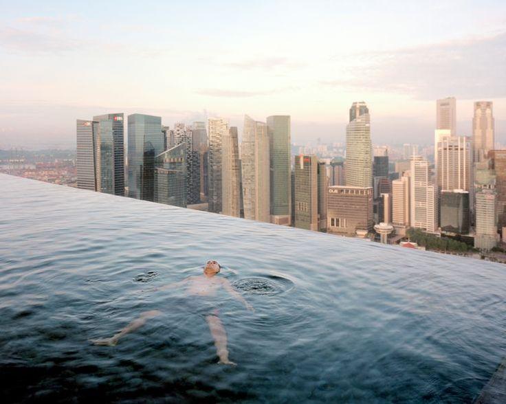 Un homme flotte dans la piscine située au 57e étage du Marina Bay Sands Hotel. Derrière lui, « Central », le quartier de la finance de Singapour. Singapour. [Avec l'aimable autorisation des artistes]