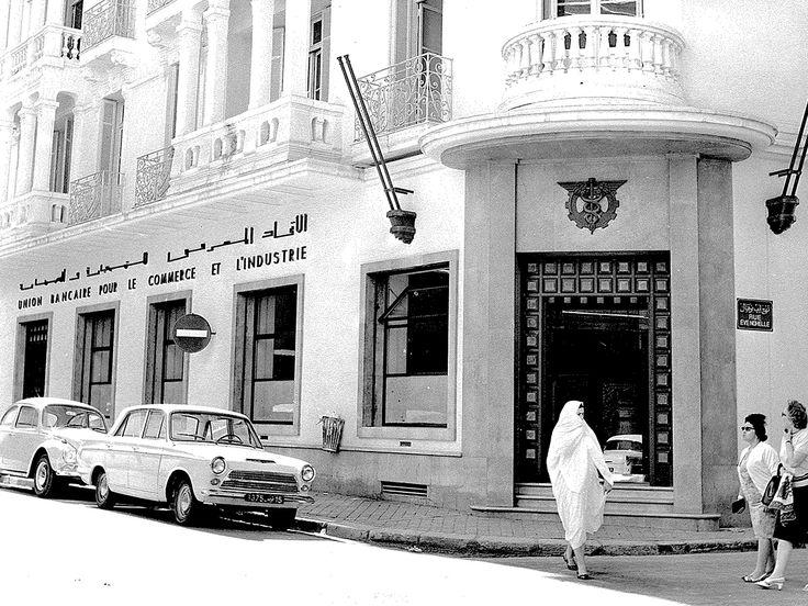 Vue d'une agence de Tunis de l'UBCI (Union bancaire pour le commerce et l'industrie – Groupe BNP Paribas) en 1966. Les deux voitures garées à côté de l'agence sont, de gauche à droite: une Volkswagen Coccinelle de 1963, une Ford Cortina Mark I 4 portes avec nouvelle calandre de 1962 (de Ford Grande Bretagne).