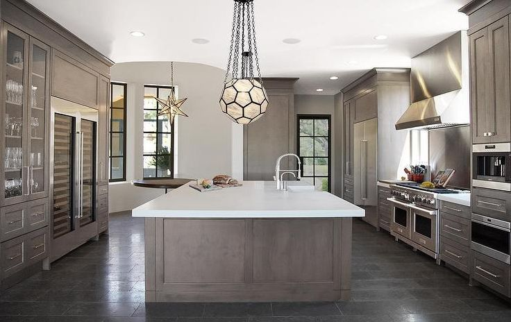 Contemporary kitchen features gray wash island topped with thick white quartz fitted with a ...