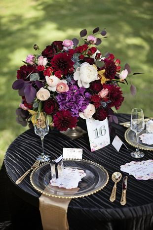 Romantic centerpiece idea for fall wedding - red, white and pink lush floral centerpiece on black, satin table linens and gold napkins {Nicolette Moku Photography}