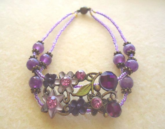 Add some color to brighten your day!  This gorgeous purple, handmade multi-strand cuff bracelet features oodles of natural violet amethyst, gold-plated fittings and a moulded brass centerpiece covered in a riot of pink and purple flowers. Enjoy!