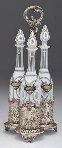 silver & gold, Continental, Continental, 19th century, silverplated Victorian liquor caddy with three-lobed base with reticulated and chased scrolling floral design set on scrolled foliate feet. Includes a set of three Bohemian glass cut-to-clear long necked decanters with stoppers and sterling silver liquor labels, each marked STERLING on reverse.