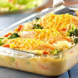 Moist, tender chicken breasts covered with melted cheddar cheese, sitting on a bed of creamy rice and vegetables.
