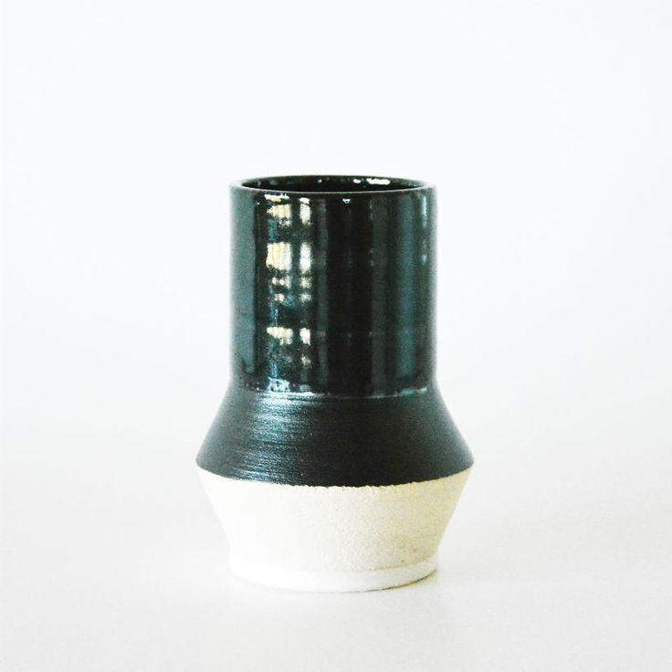 Handthrown stoneware vase w. black slip and black tenmoku glaze, white glaze on foot. The light color on the lower half of the vase is the raw clay. H: 13,50 cm.Dia: 7 cm.One of a kind!