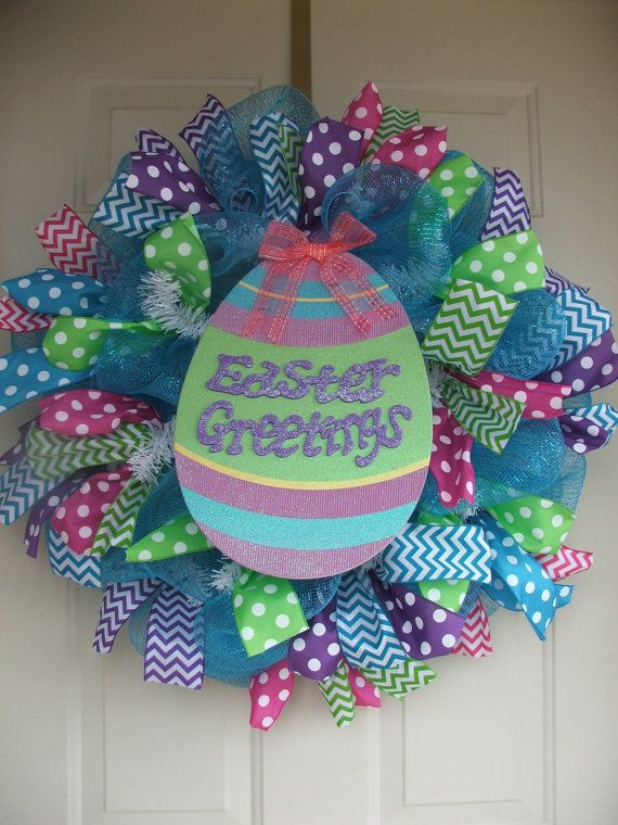 Easter Greetings wreath features turquoise mesh on a white work wreath. It has an attached glittered cardboard Easter Greetings Sign in the