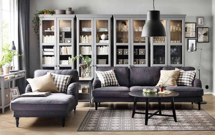 A living room with a grey 3.5-seat sofa, chaise longue and a black round coffee table. Combined with four grey glass-door cabinets.