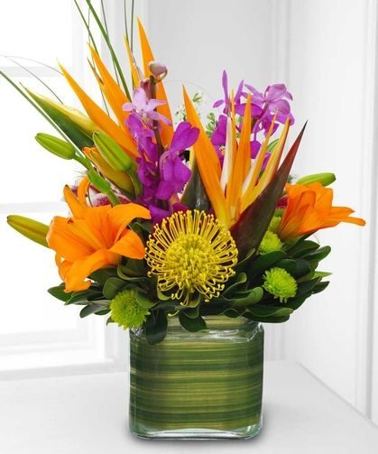 Cube of Paradise - This glass cube arrives brimming with tropical flowers. The assortment includes orchids, birds of paradise and protea. The vase is lined with tropical foliage.